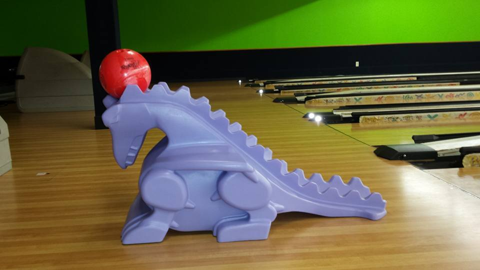Dinosaur bowling ball helper on lanes